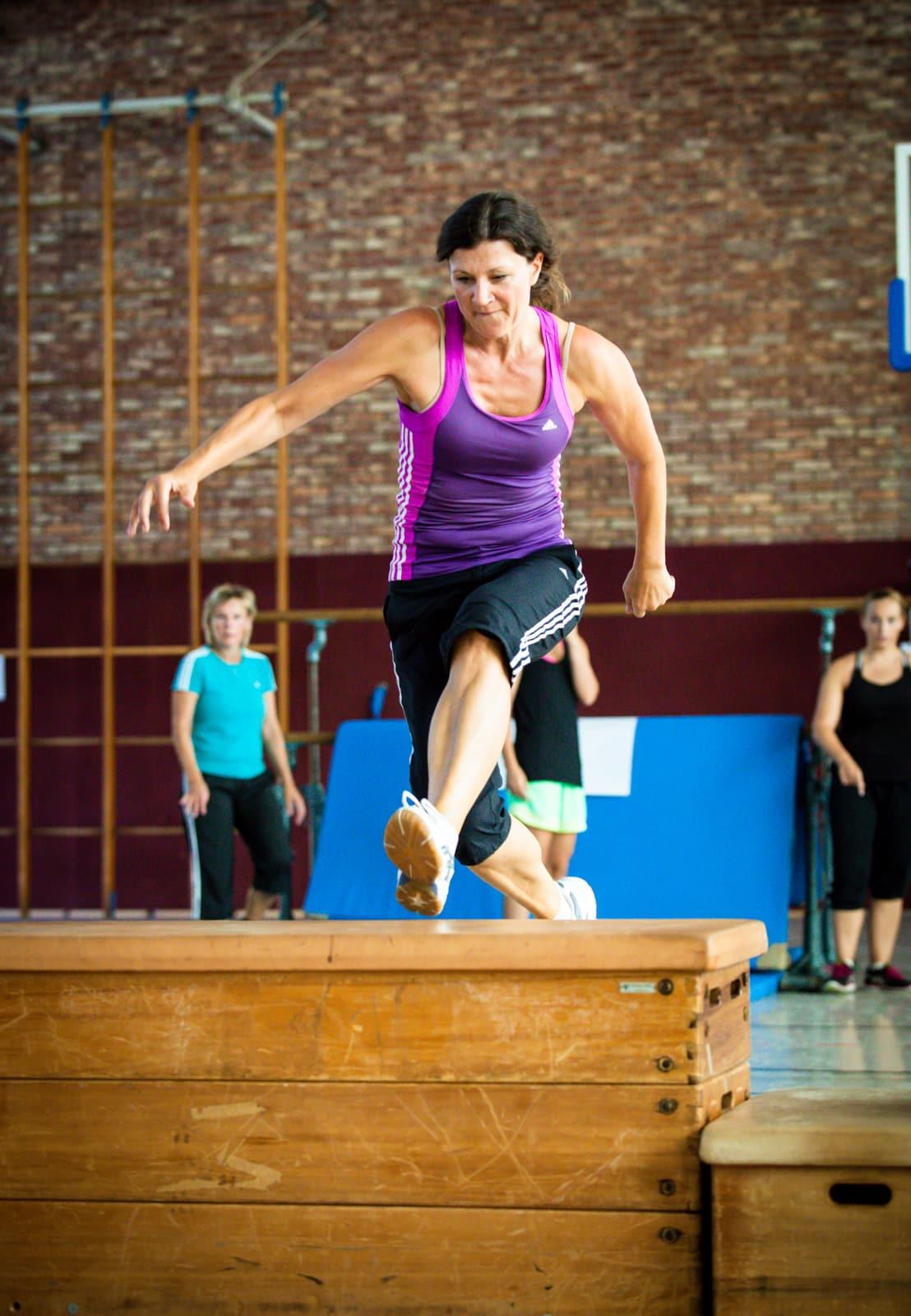 Sportlehrerin springt über einen Kasten