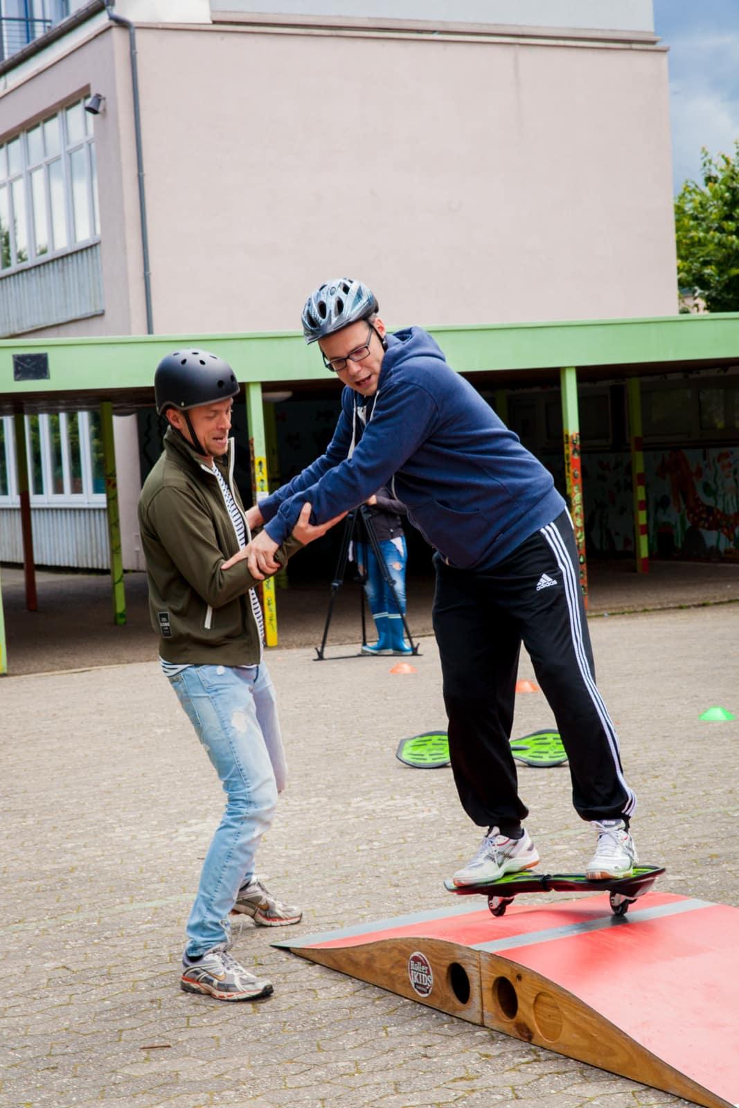 Lehrer helfen sich beim Waveboard fahren