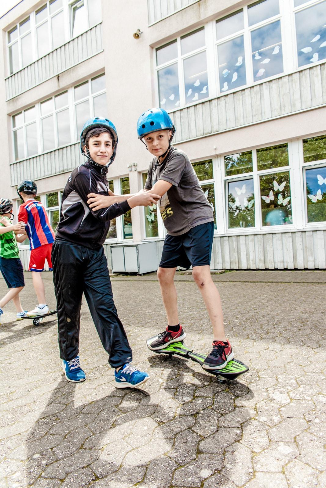 Zwei Jungs unterstützen sich beim Lernen eines Waveboards