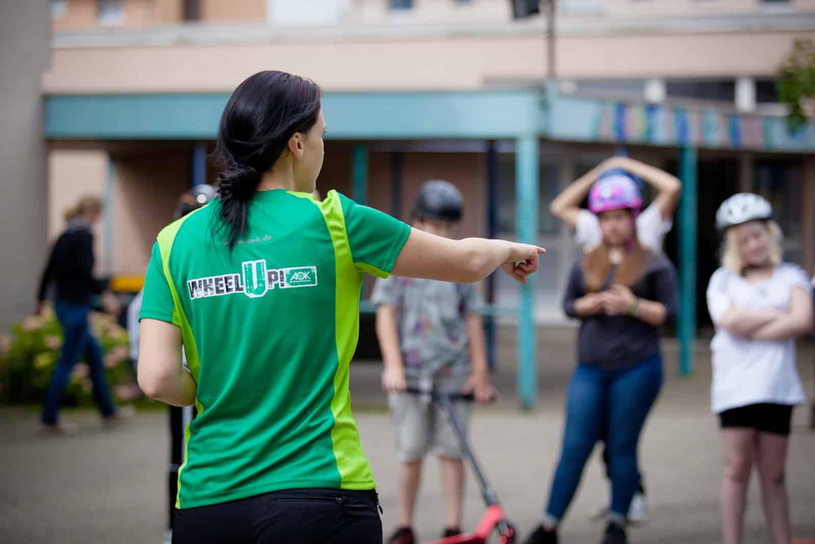 Eine Trainerin von AOK Wheel up instruiert Kinder