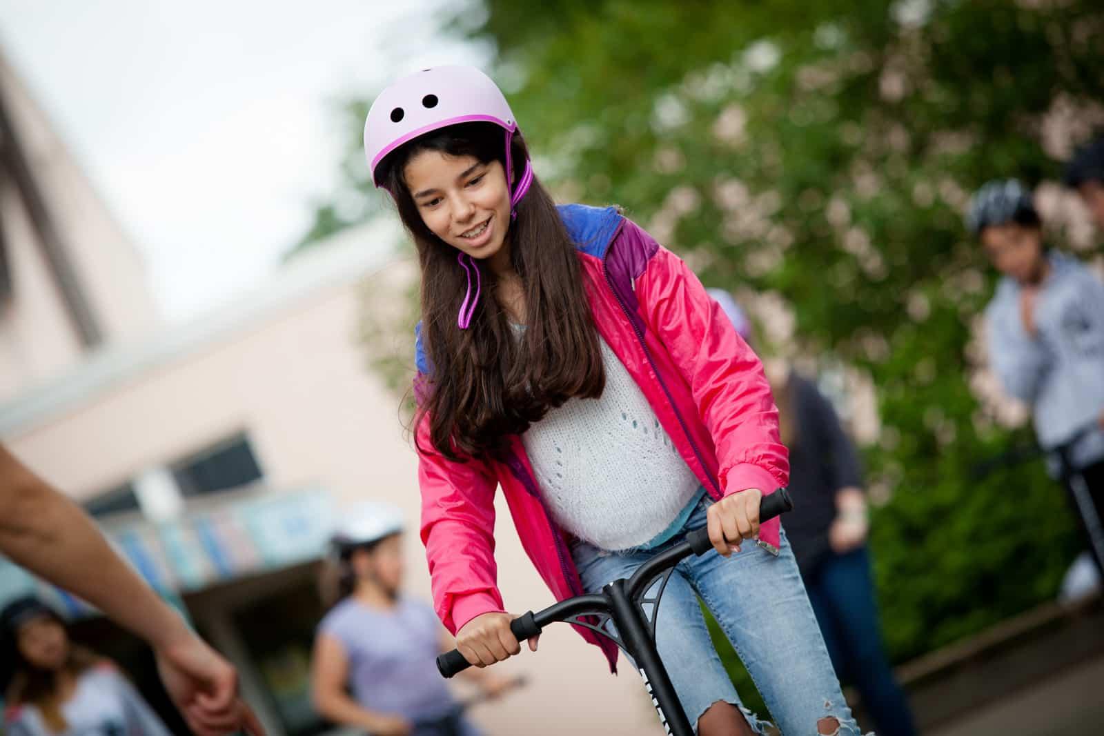 Ein Mädchen mit rosa Helm fährt Scooter