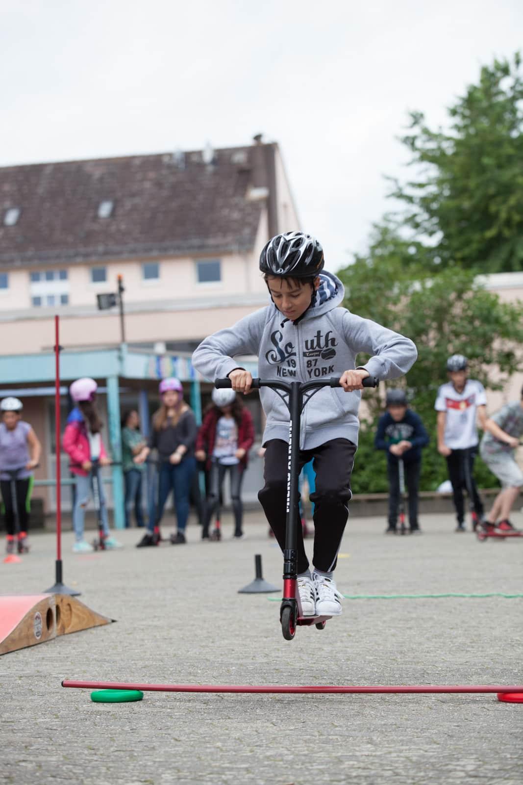Ein Junge springt mit seinem Mini Scooter über einen Stab