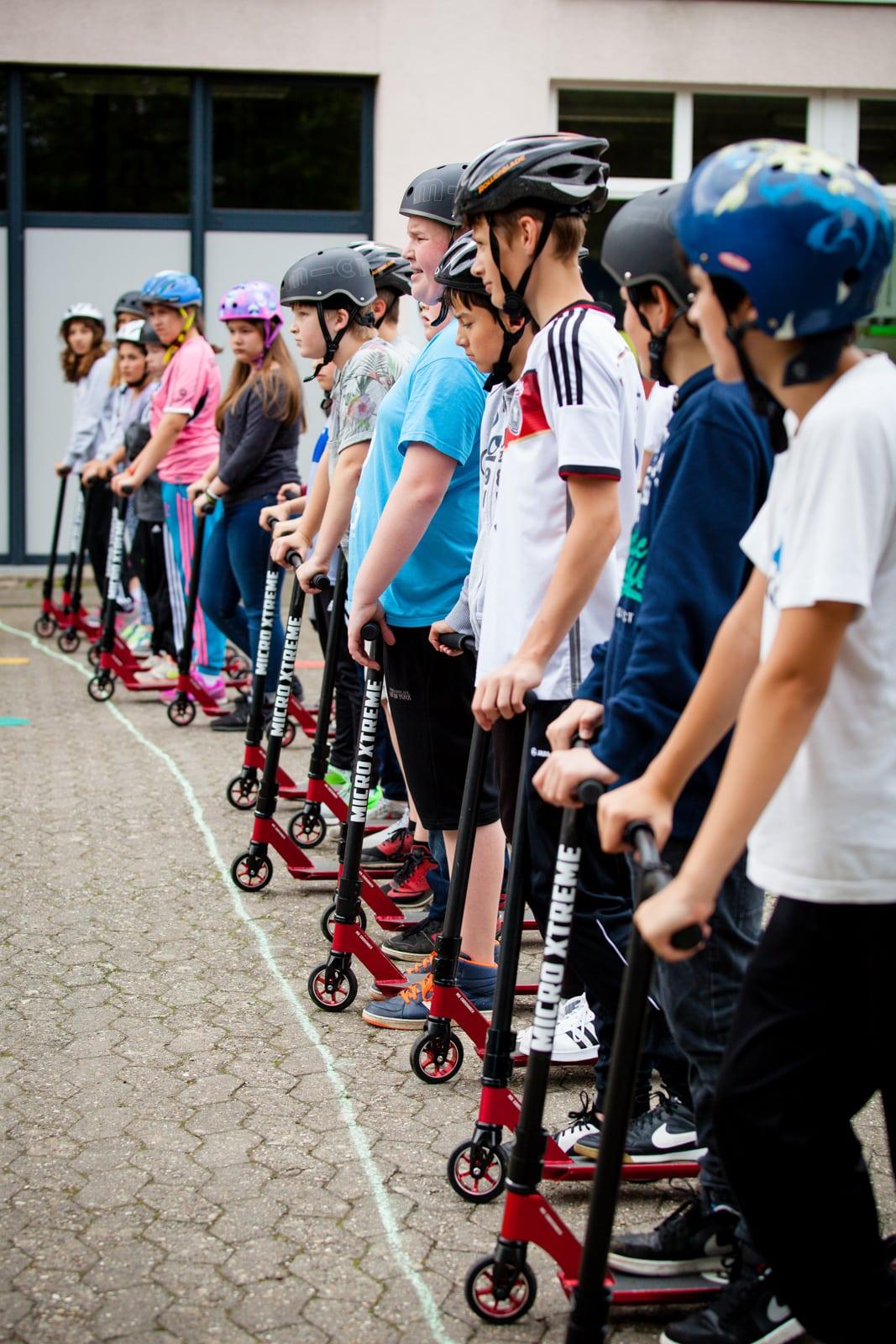 Kinder stehen mit ihren City Skate Wheel up Scootern an einer Startlinie