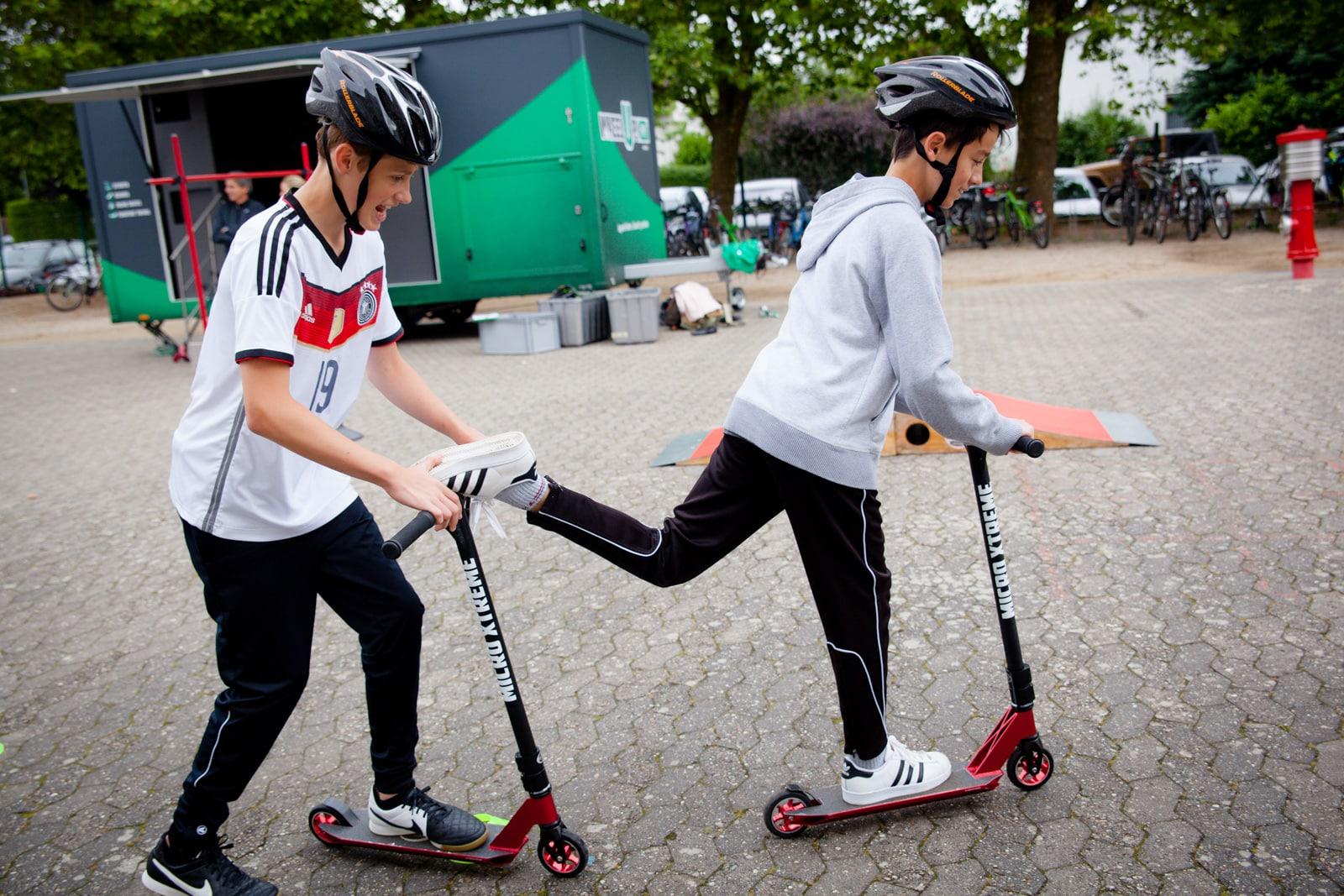 Zwei Jungs üben das einbeinige Rollerfahren