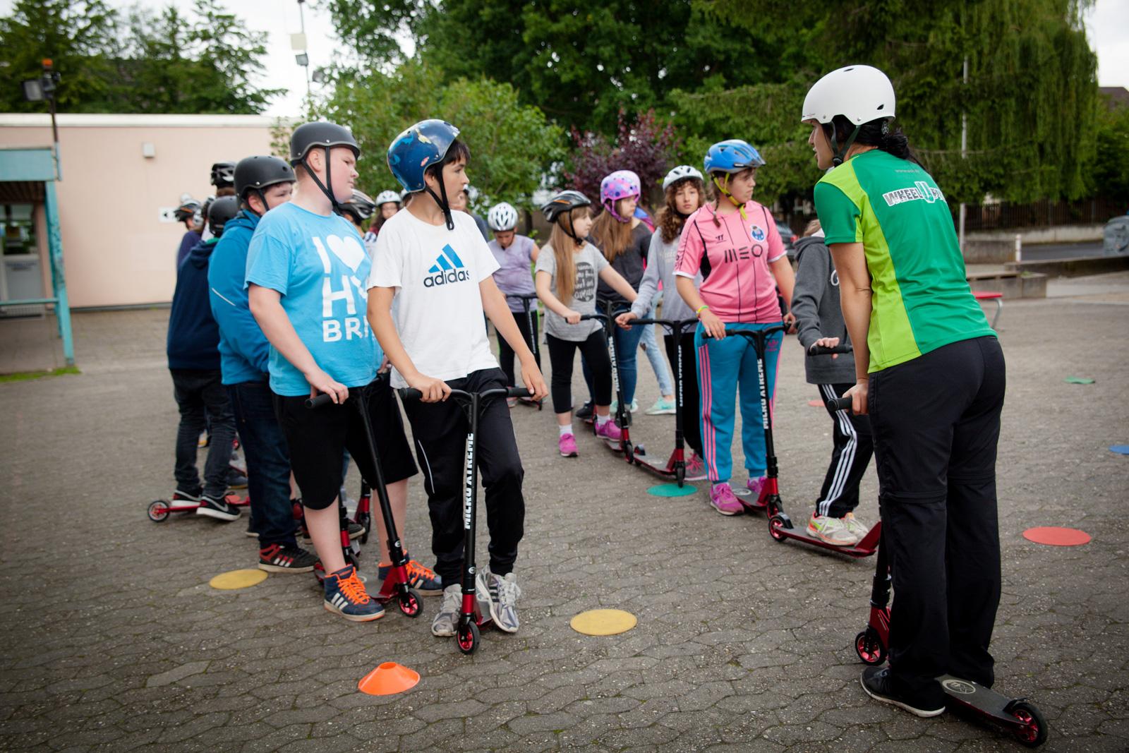 Schüler stehen mit ihren Wheelup Scootern in zwei Reihen und bekommen Anweisung von einer Trainerin