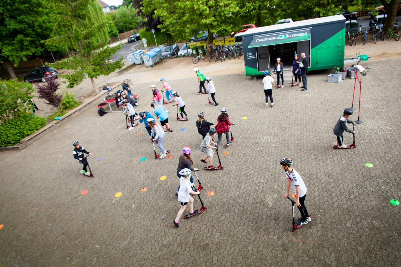 Kinder fahren mit ihren Rollern auf dem Schulhofparcour von Wheel up AOK Hessen
