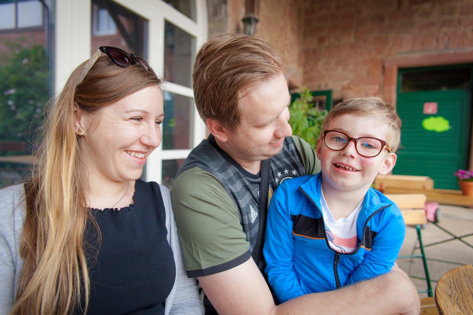 Eine dreiköpfige Familie lacht