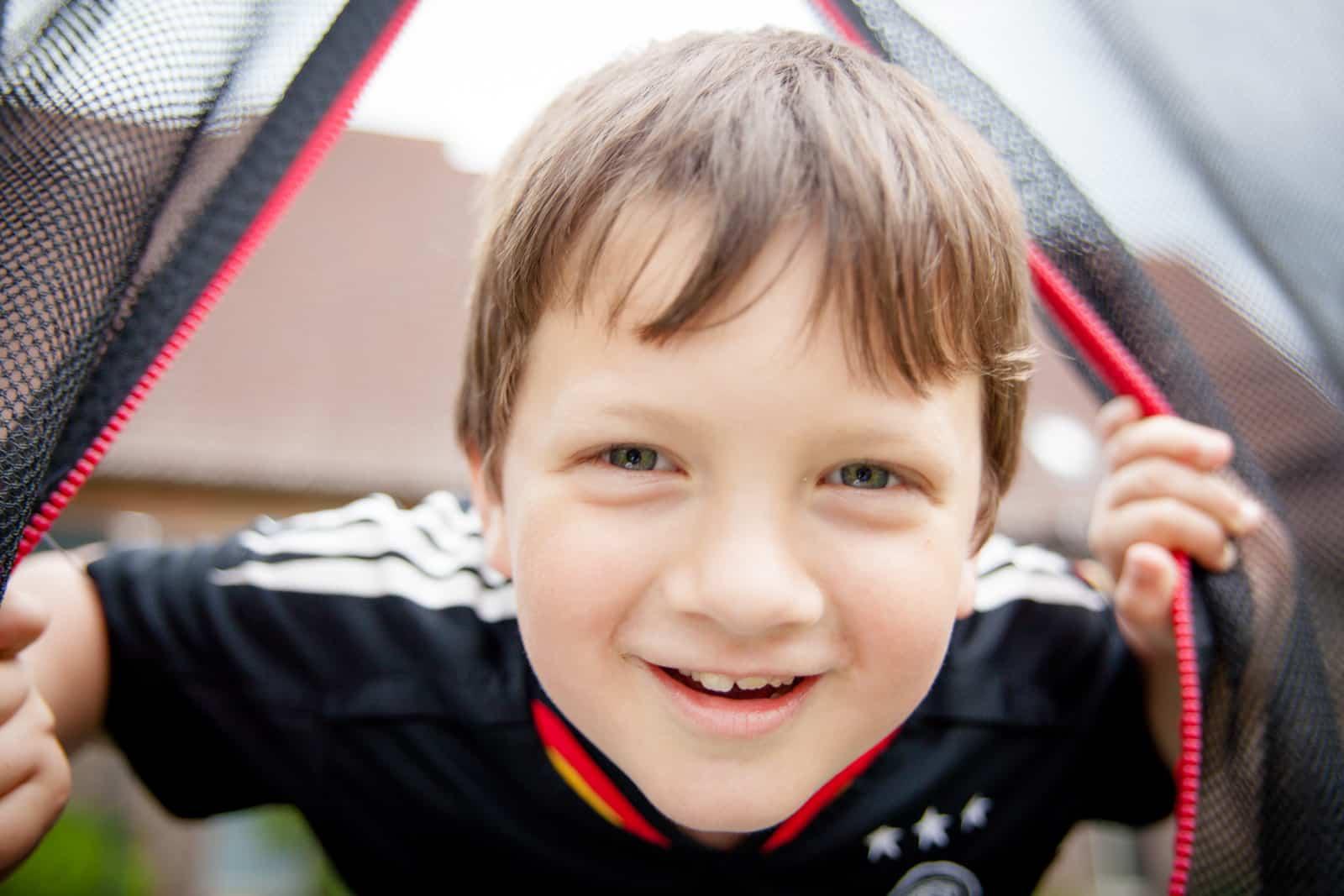 Ein Junge lacht sehr nah in die Kamera