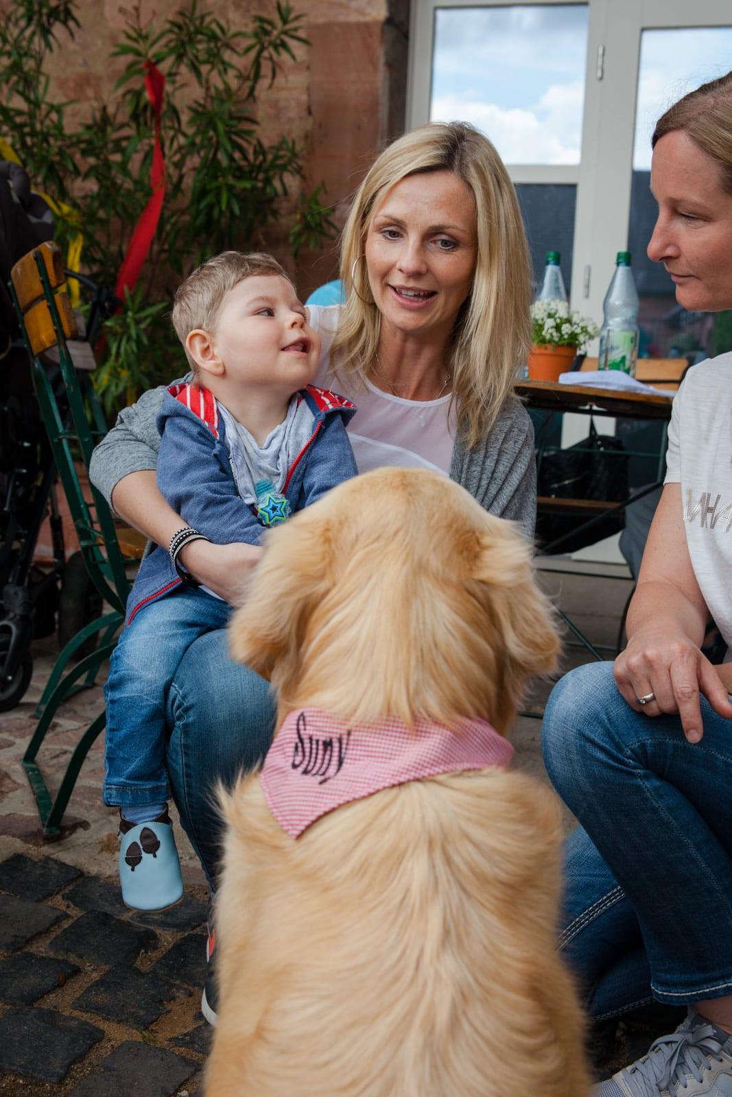 Eine Frau hat ihr Kind auf dem Schoss und ein Hund sitzt vor ihr
