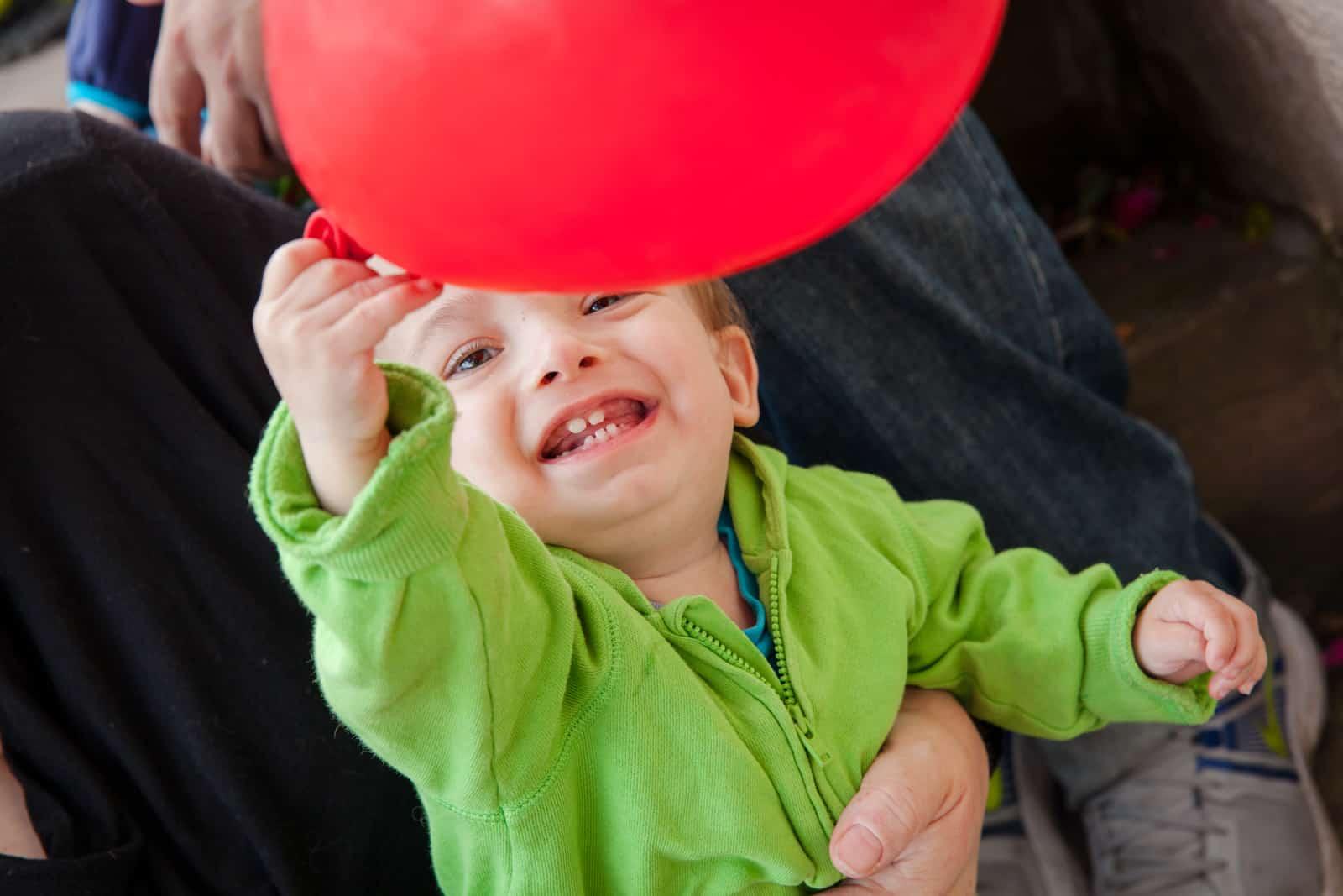 Ein Kind spielt mit einem roten Ballon