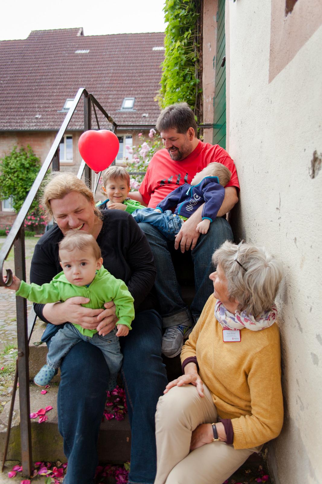 Eine Familie mit ihren Kindern sitzt auf einer Treppe