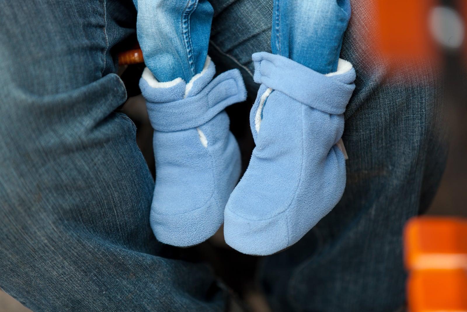 Kleine Kinderfüsse in Kuschelschuhen in blau.