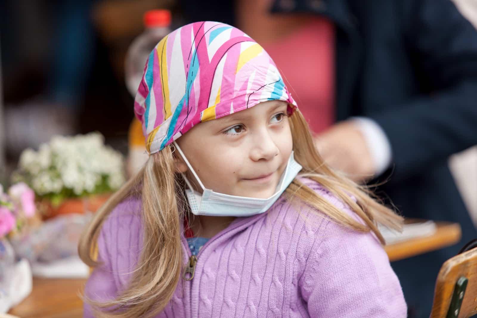 Ein Kind mit Kopftuch und Maske