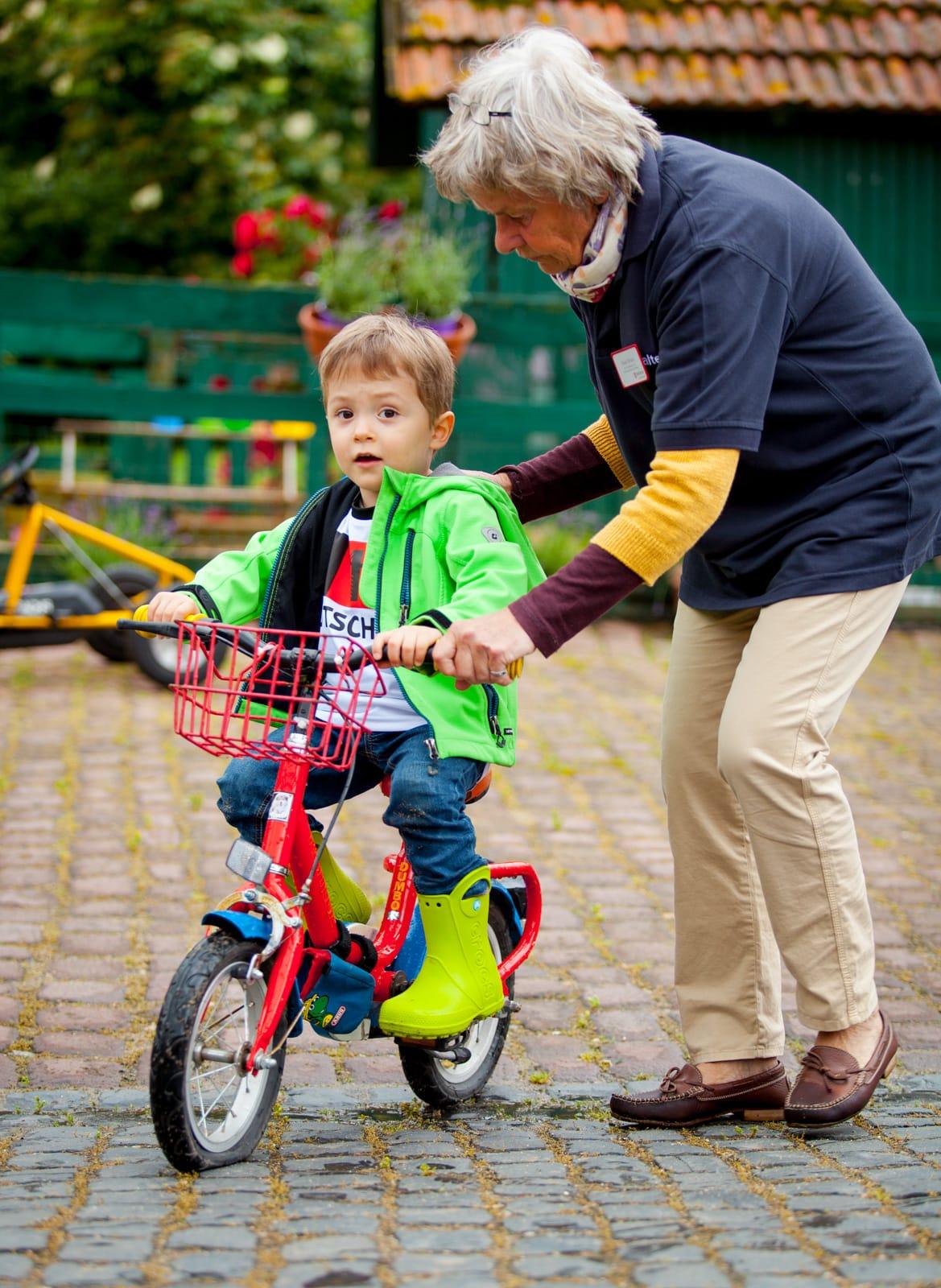 Ein kleines Kind fährt Fahrrad und wir von einer Frau unterstützt