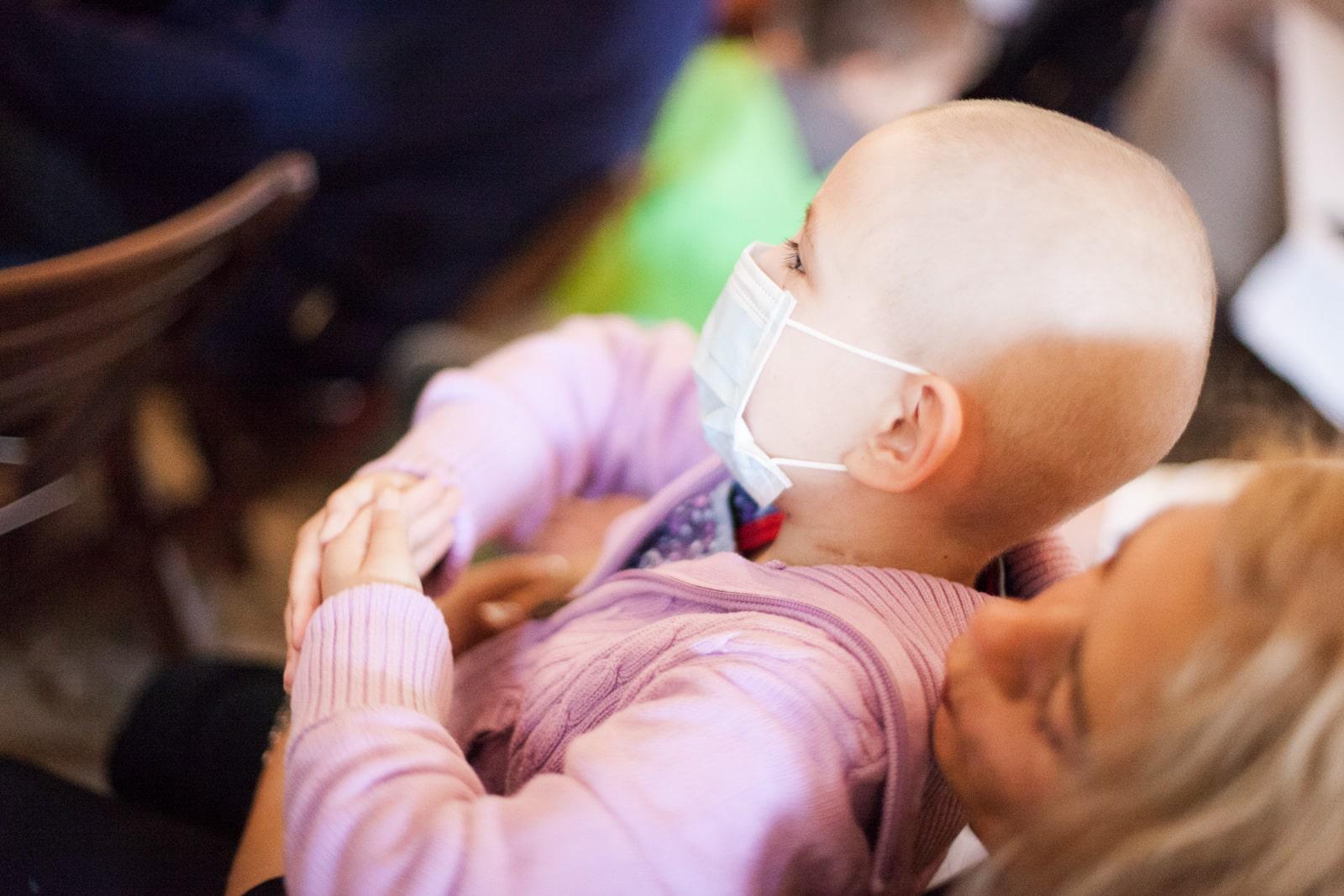 Ein krankes Kind ohne Haare auf dem Schoss seiner Mutter