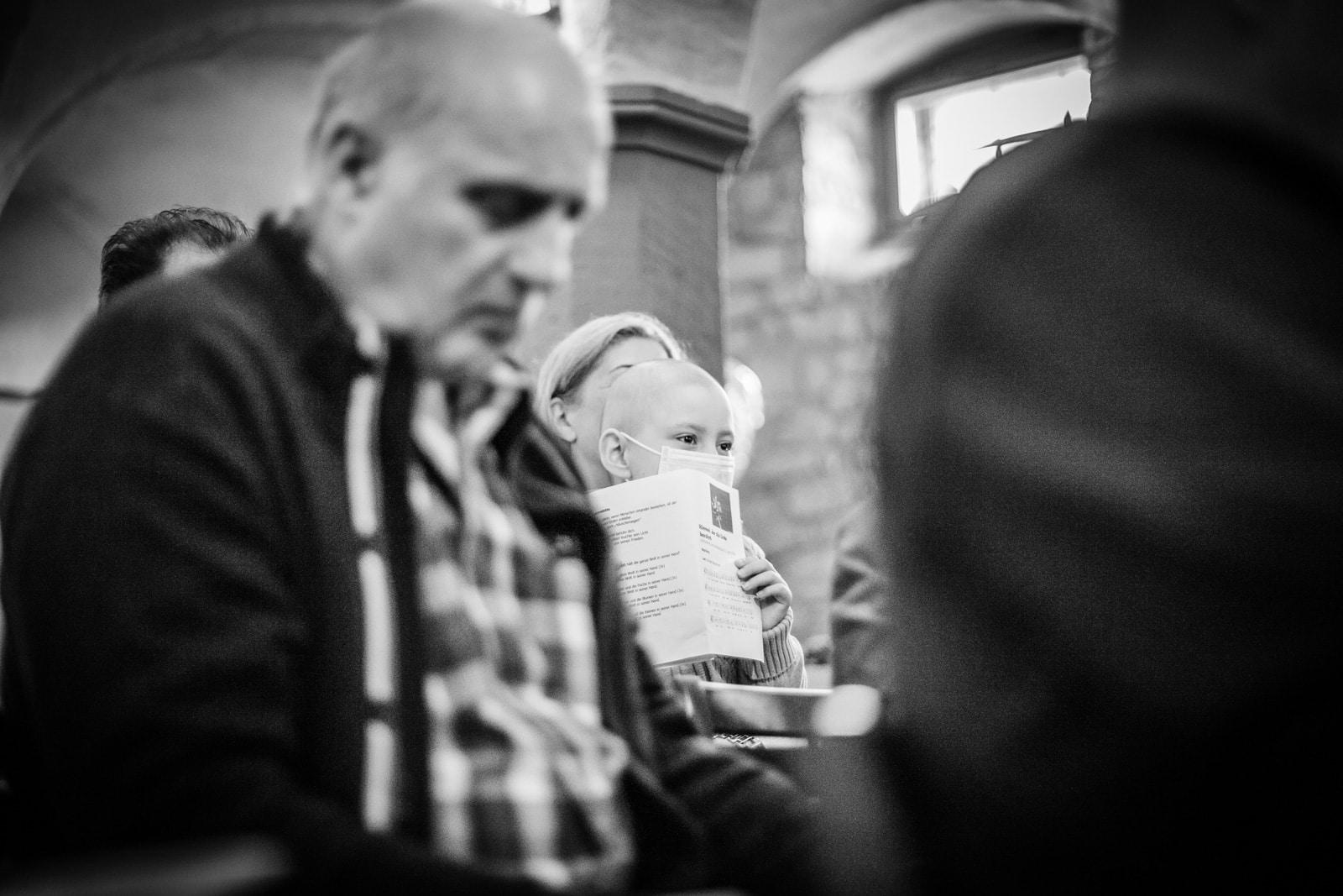 Ein Kind hört mit seinen Eltern beim Gottesdienst zu
