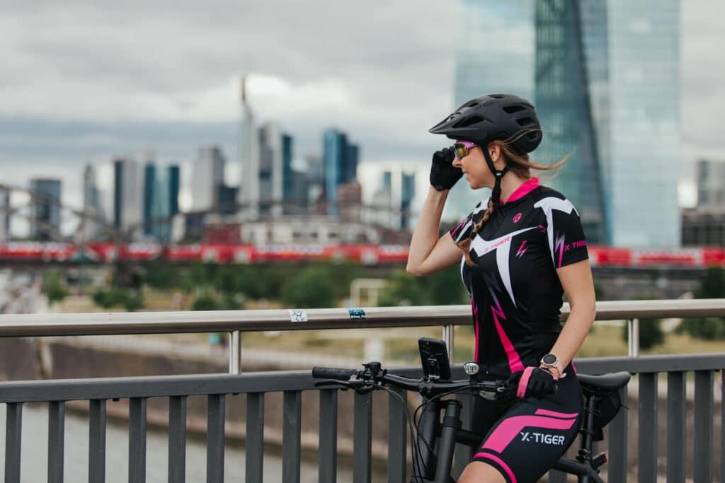 Frau steht mit Fahrradhelm und x-tiger Fahrradbekleidung und schaut auf den Main in Frankfurt im Hintergrund eine S-Bahn und die EZB