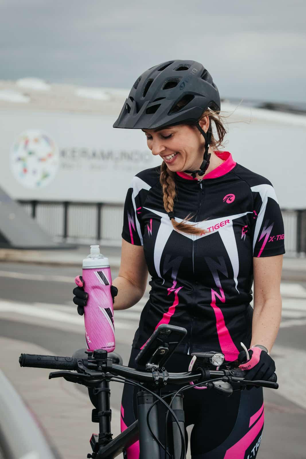 Frau lacht und hält ihre pinke Fahrradflasche fest