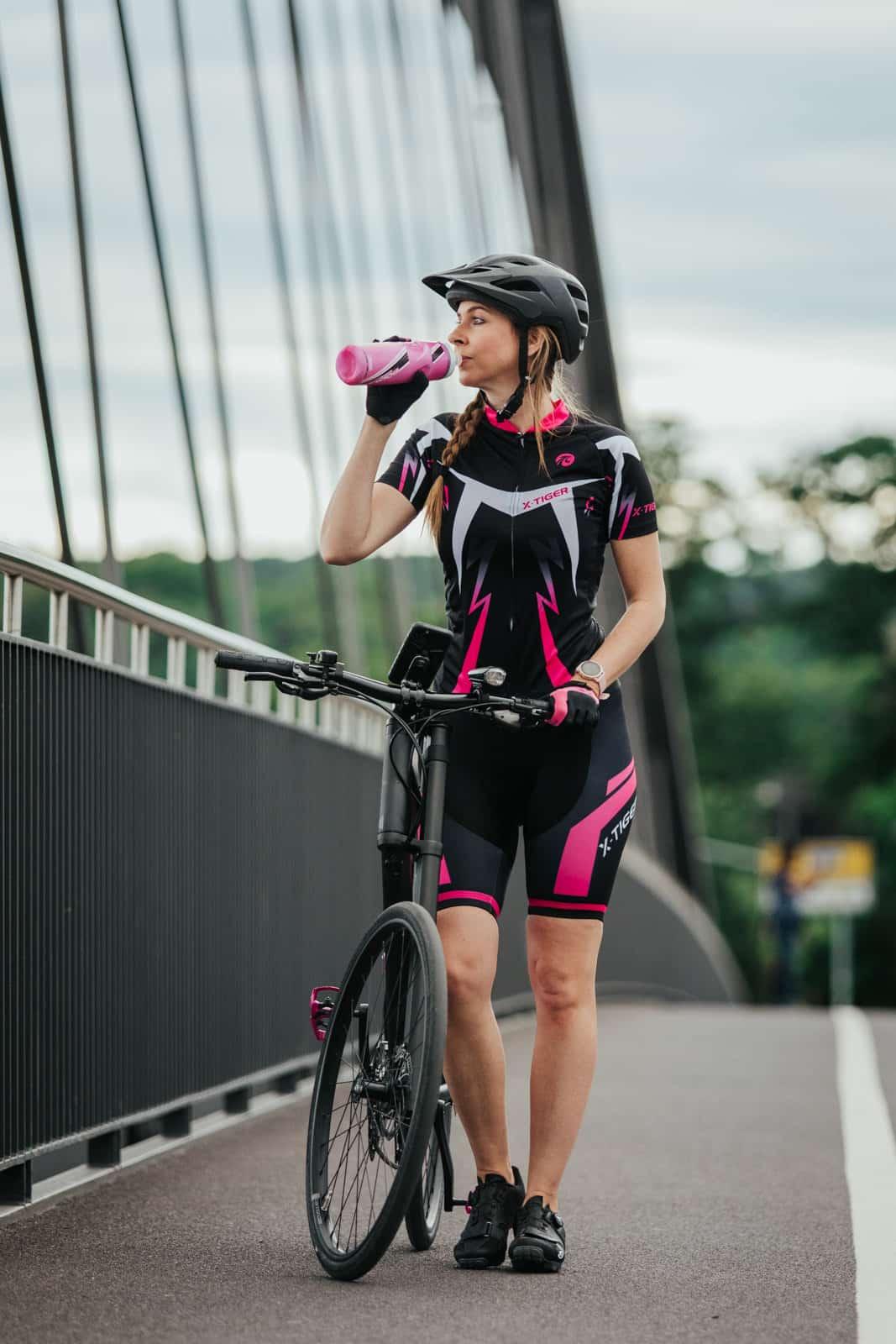 Frau trinkt aus ihrer pinken Fahrradflasche
