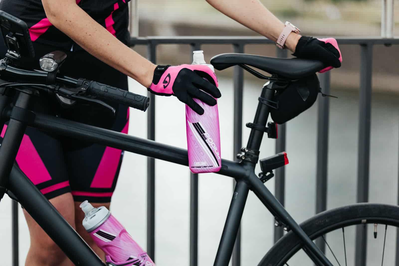 Frau greift nach pinker Trinkflasche an ihrem schwarzen Cannondale Fahrrad