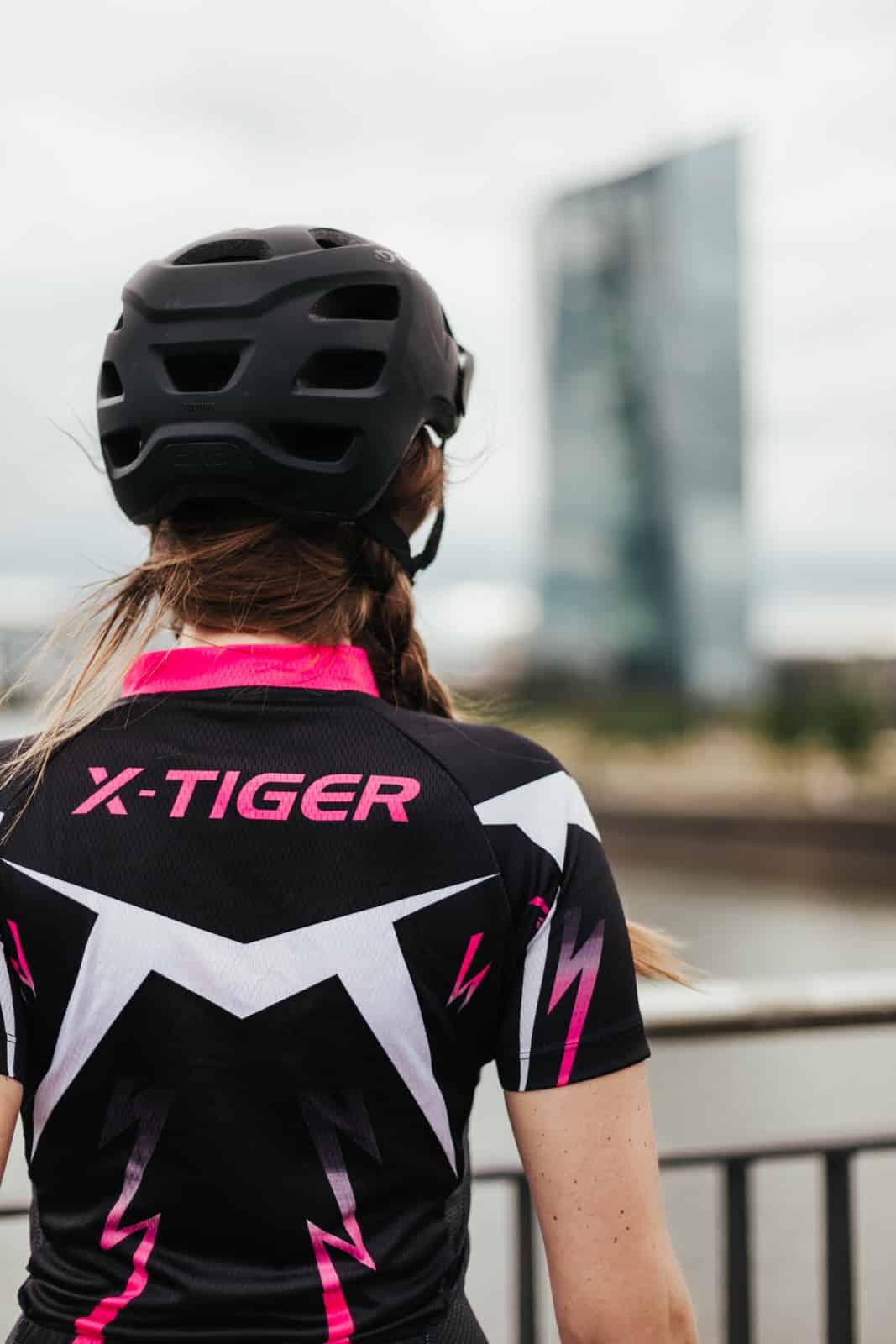 Frau von hinten mit Fahrradhelm in schwarz und x-tiger Oberteil