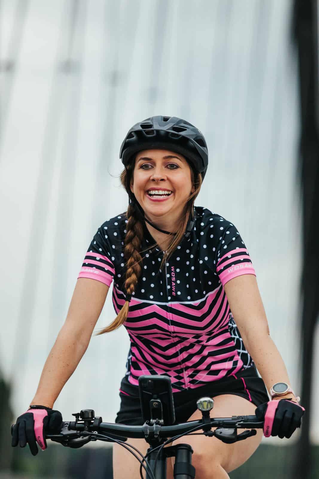 Frau fährt lachend mit pinkem Fahrradoberteil und Cannondale Fahrrad in Frankfurt