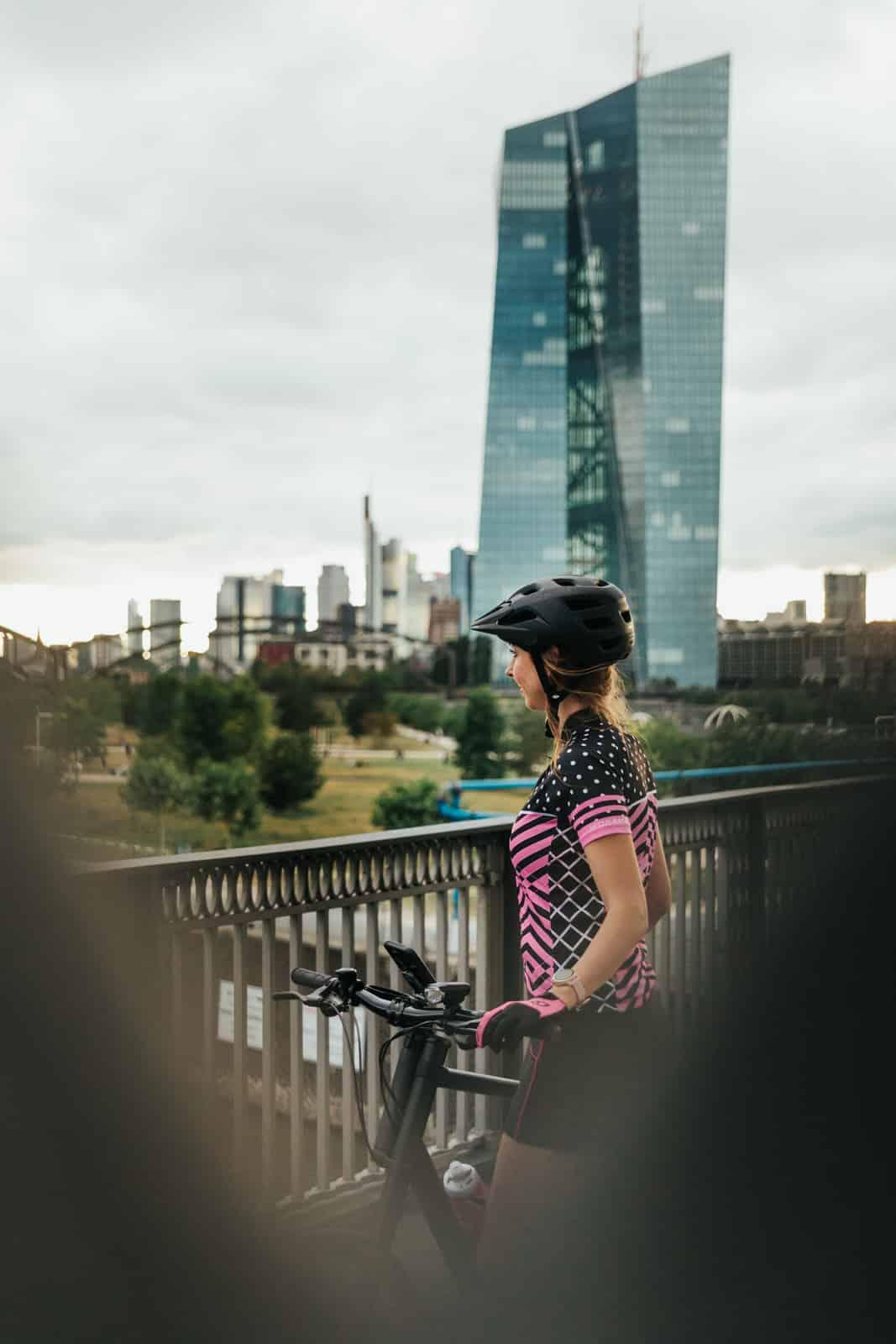 Frau steht mit ihrem Cannondale Fahrrad auf der Honsellbrücke in Frankfurt