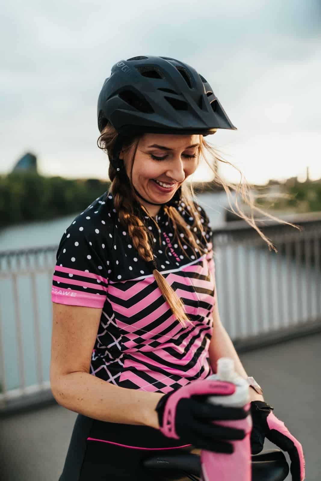 Model in Fahrradkleidung lacht bei untergehender Abendsonne in Frankfurt am Main mit Trinkflasche in Pink in der Hand