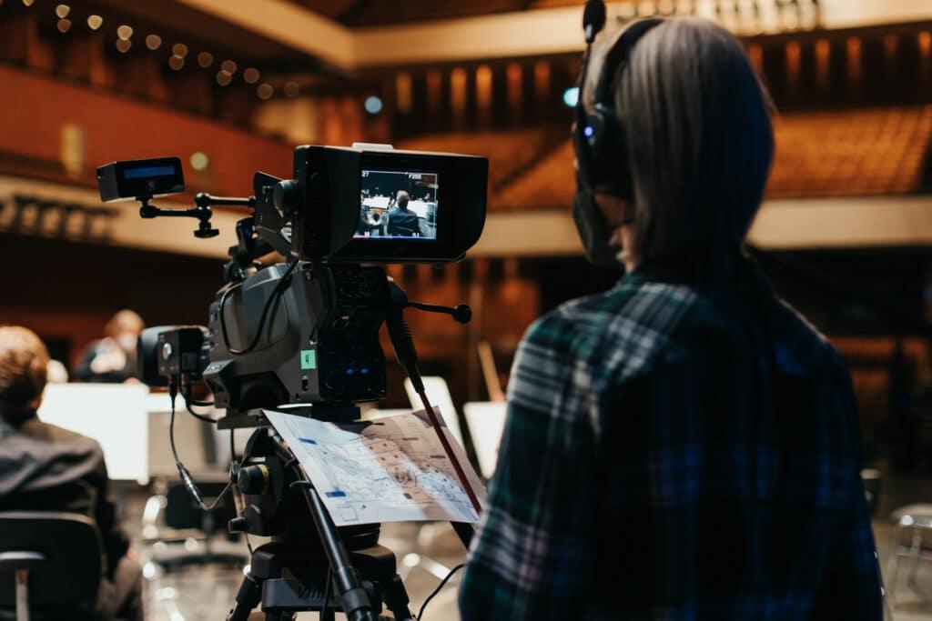 Kamerafrau steht hinter einer Livekamera für einen Konzertstream